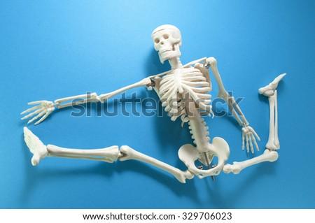 Skeleton model action on blue background. - stock photo
