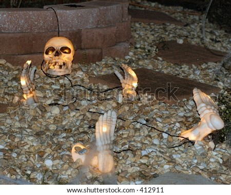Skeleton rising from the grave at Halloween. - stock photo