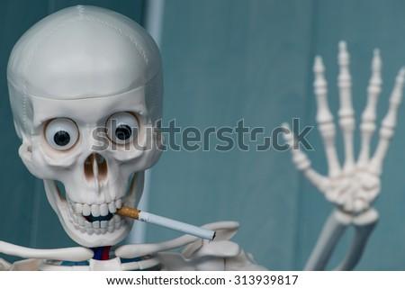 Skeleton smoking cigarette. Focus on cigarette  - stock photo