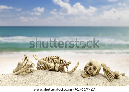 skeleton with skull   on sand ,blue sky with sea background. - stock photo