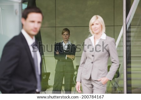 Skeptical business people standing in office building - stock photo