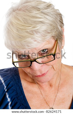 Skeptical white haired mature lady showing her doubt with an expressive face looking down over the rims of her glasses. - stock photo