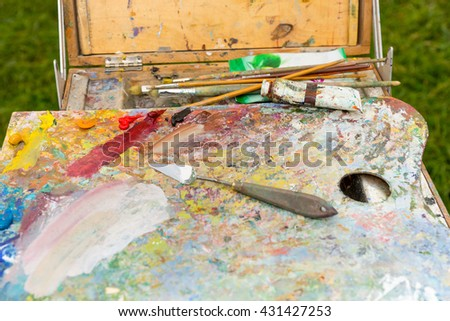 Sketchbook with different artist's equipment colorful palette paletteknife paints and paintbrushes outdoors - stock photo