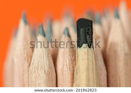 Sketching pencil with thick graphite among a bunch of regular inexpensive wooden drawing pencils on vivid orange background, symbolizing individuality concept, creative design and artistic approach - stock photo