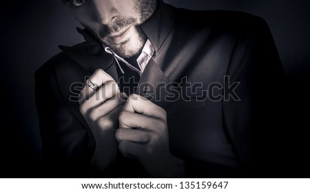 Skewed studio fashion portrait of a rough unshaven young man in elegant formal suit with hand ring accessory - stock photo
