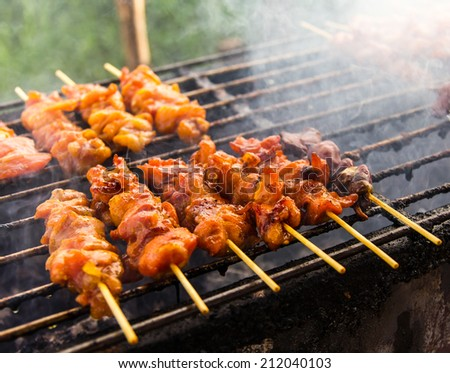 Skewer chicken pieces roasting on the grill and smoke  - stock photo