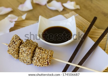 Skewer of three pieces of red tuna with sesame, on white plate accompanied by small bowl with soy sauce and chopsticks decoration - stock photo