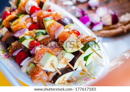Skewered on wooden sticks tasty pork meat and vegetables mix shashlik prepared for grilling on plate in the kitchen close up - stock photo