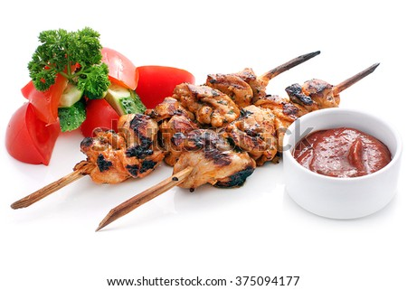 Skewers of chicken with vegetables: cucumbers, tomatoes, cilantro and tomato sauce. Isolated on a white background. - stock photo