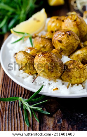 Skewers of mushrooms with a side dish of rice - stock photo