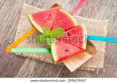 Skewers of watermelon on wooden table, rustic style - stock photo