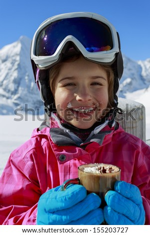 SKI, Apres ski, winter, child - young skier drinking hot chocolate  in winter resort - stock photo