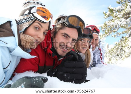Ski couples lying in the snow - stock photo