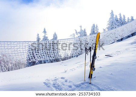 Ski equipment on ski run with pine forest covered in snow seen trough a frozen fence on back in winter season - Poiana Brasov - stock photo