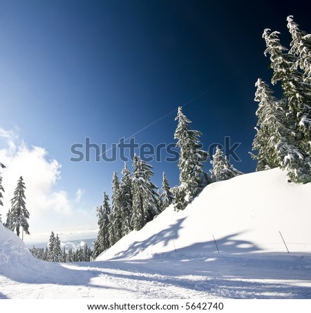 Ski hill following an overnight snowfall with an airplane contrail heading towards the airport - stock photo