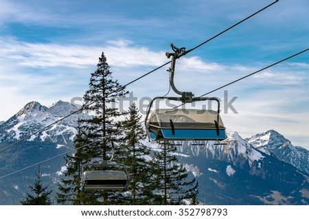 Ski lift chairs on snowy Alps background  Ski lift chairs in Ehrwald, Austria on a winter background with snowy mountain peaks - stock photo
