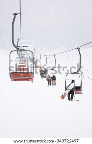 Ski lift in the fog, with skiers  - stock photo