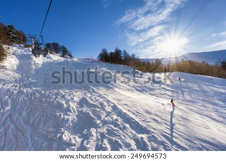 Ski lift over slopes in mountain with paths from skies and snowboards - stock photo