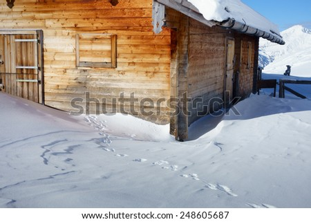 Ski lodge and cottage in the snowy Alps - stock photo
