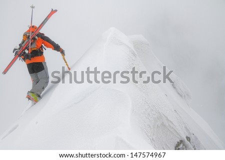 Ski mountaineer ascending a mountain in bad weather - stock photo