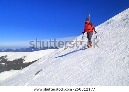 Ski mountaineer carries touring skies on the back while traversing a steep area - stock photo