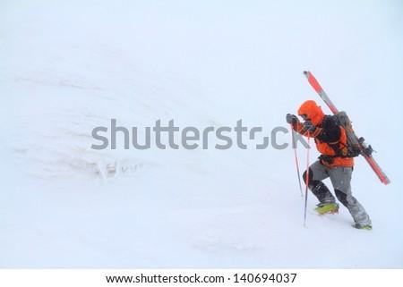 Ski mountaineer climbing a mountain in bad weather - stock photo
