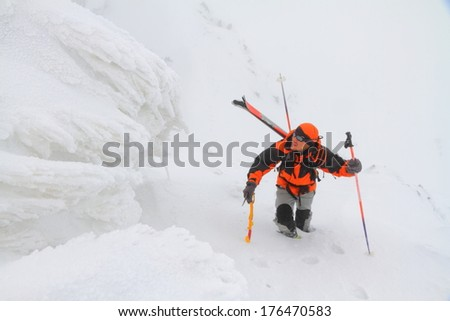 Ski mountaineer climbs icy slope in adverse weather - stock photo