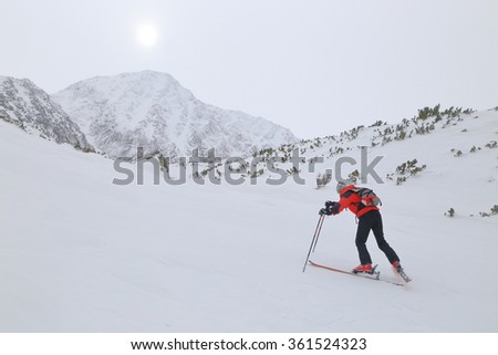 Ski mountaineer struggles to climb in harsh weather  - stock photo