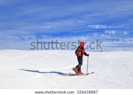 Ski mountaineer traversing a snow covered plateau in sunny winter day - stock photo