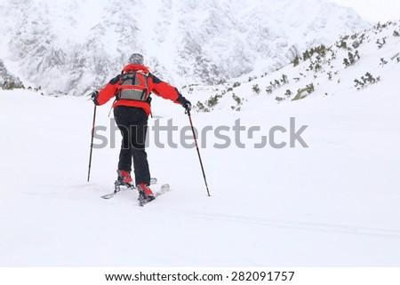 Ski mountaineer woman climbing on touring skis under snowfall  - stock photo