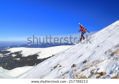 Ski mountaineer woman descending a steep slope with skies on the backpack - stock photo