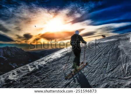 Ski mountaineering silhouette, girl with a dog in the distance - stock photo