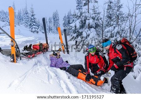 Ski patrol team rescue woman skier with broken leg - stock photo