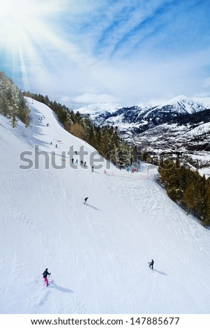 Ski resort in Andorra with skiers sliding down the slope - stock photo