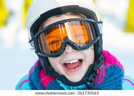 Ski, skier girl, winter vacation, snow, skier, sun and fun - portrait of happy girl in goggles enjoying ski - stock photo