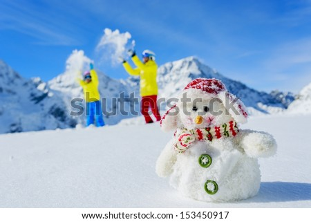 Ski, skier, sun and winter fun - skiers with snowman enjoying winter holidays - stock photo