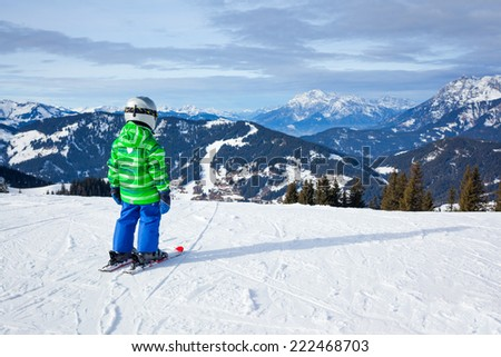 Ski, skier, winter - back view of lovely small boy has a fun on ski - stock photo