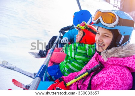 Ski, skiing - Skier girl with her brother on ski lift - stock photo