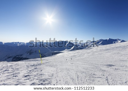 Ski slope and blue sky with sun. Caucasus Mountains, Georgia, ski resort Gudauri. - stock photo