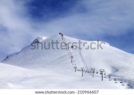 Ski slope and chair-lift at morning. Caucasus Mountains. Georgia, ski resort Gudauri, Mt. Kudebi. - stock photo