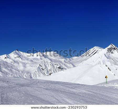 Ski slope and warning sign. Caucasus Mountains, Georgia, ski resort Gudauri. - stock photo