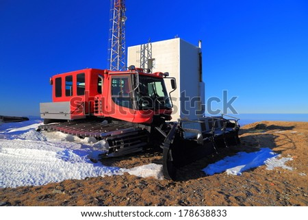 Ski slope grooming machine parked on the mountain in absence of snow - stock photo