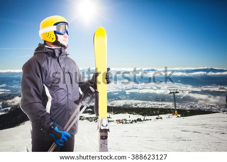 Ski slope in High Tatras mountains on the background and skier portait with equipment - stock photo