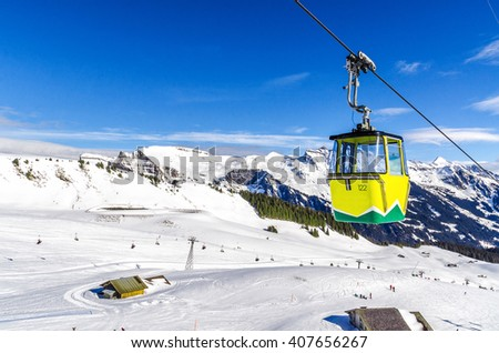 ski slope in Swiss Alps in sunny day. Yellow cable car above and mountains behind, skiing resort in Alps Switzerland, ''Jungfrau'' - stock photo