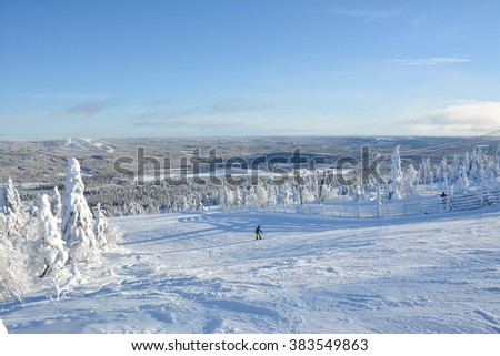 Ski slopes and snow covered trees on sunny day in Lapland Finland - stock photo