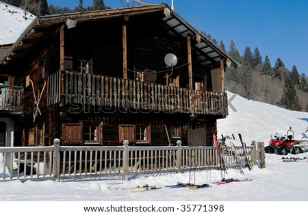 ski standing at the fence of a ski lodge - stock photo