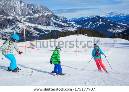 Ski, winter, snow, skiers, sun and fun - family enjoying winter vacations. Back view. - stock photo