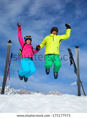 Ski, winter, snow, skiers, sun and fun - family enjoying winter vacations. Father with his daughter jumping against blue sky. - stock photo