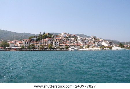 Skiathos Town, Greece, seen from just off-shore. Buildings are huddled together on a small hill. - stock photo