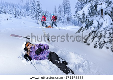 Skier after accident waiting for mountain rescue lying in snow - stock photo